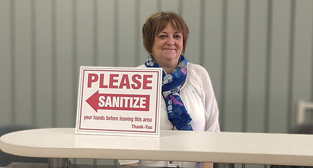"Sherri Harrison at UH Information Desk with ""Please Sanitize"" sign"