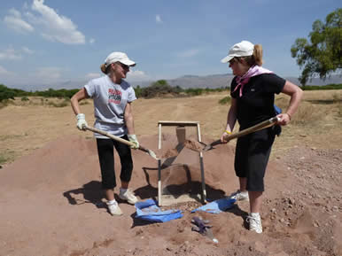 Linda Pera (right) and her sister Kim Riordon shovel dirt for a Habitat for Humanity build in Cochabamba, Bolivia.