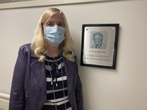 Dr. Mary Moore beside picture of Dr. David Boyd, both founders of the clinic