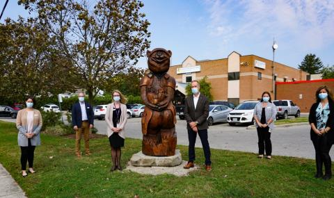 Posing with the new Dr. Tree-age sculpture outside of the Victoria Family Medical Centre are, from left: Erin Chapman, VFMC Medical Secretary; Tim Rice, Director, Medicine and Family Medicine at Victoria Hospital; Dr. Stacey Valiquet, VFMC Medical Director; Dr. Paul Woods, LHSC President and CEO; Kim Farrow, Operations Manager, Medicine Ambulatory Care; and Amanda Grant, VFMC Medical Secretary.
